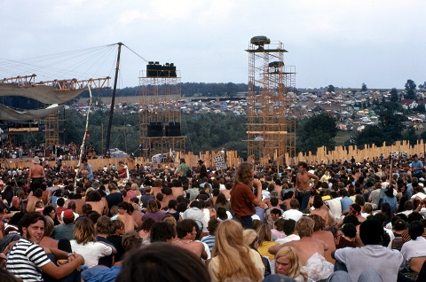 """<span style=""""font-size: 8pt; font-family: arial, helvetica, sans-serif;"""">Woodstock Music and Art Fair. The person carrying the placard is Moonfire Lewis Beach Marvin III. Joe Cocker is performing on stage. (August 17, 1969) Source: Woodstock Whisperer, <a href=""""https://commons.wikimedia.org/wiki/File:Woodstock_Music_and_Art_Fair.jpg"""">Wikimedia Commons</a> (<a href=""""https://creativecommons.org/licenses/by-sa/4.0/deed.en"""">CC BY-SA 4.0</a>)</span>"""